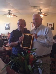 Mr. Bill Hadesty, current Chairman of the Board, presents a plaque to Fred in recognition of his outstanding service