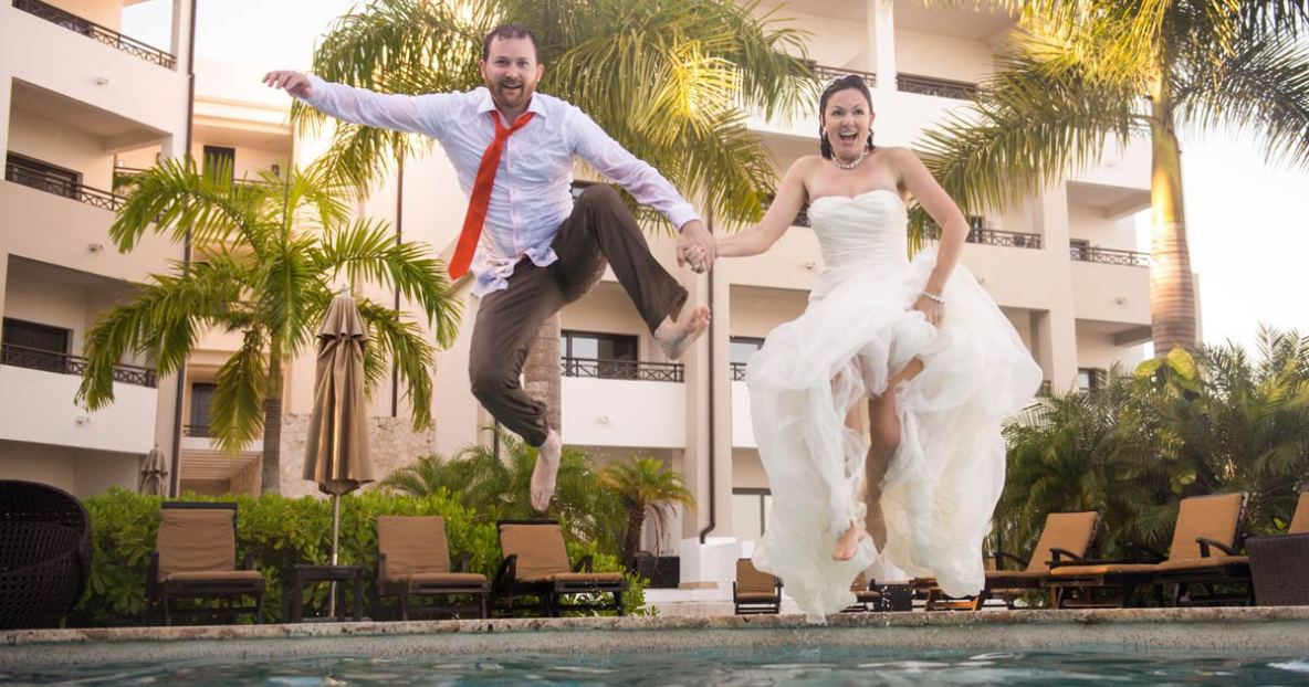 Bride and groom jumping into a pool while dressed in wedding attire on their wedding day.