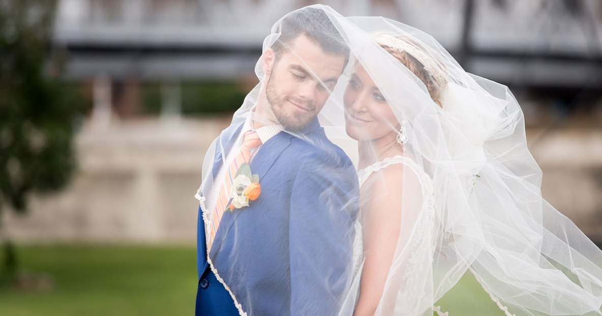 Bride and groom portrait with bride's veil covering couple.