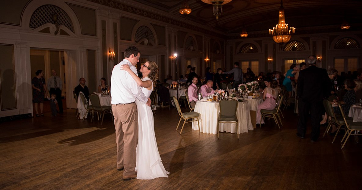 Bride and groom first dance photo at indoor wedding reception and dance.