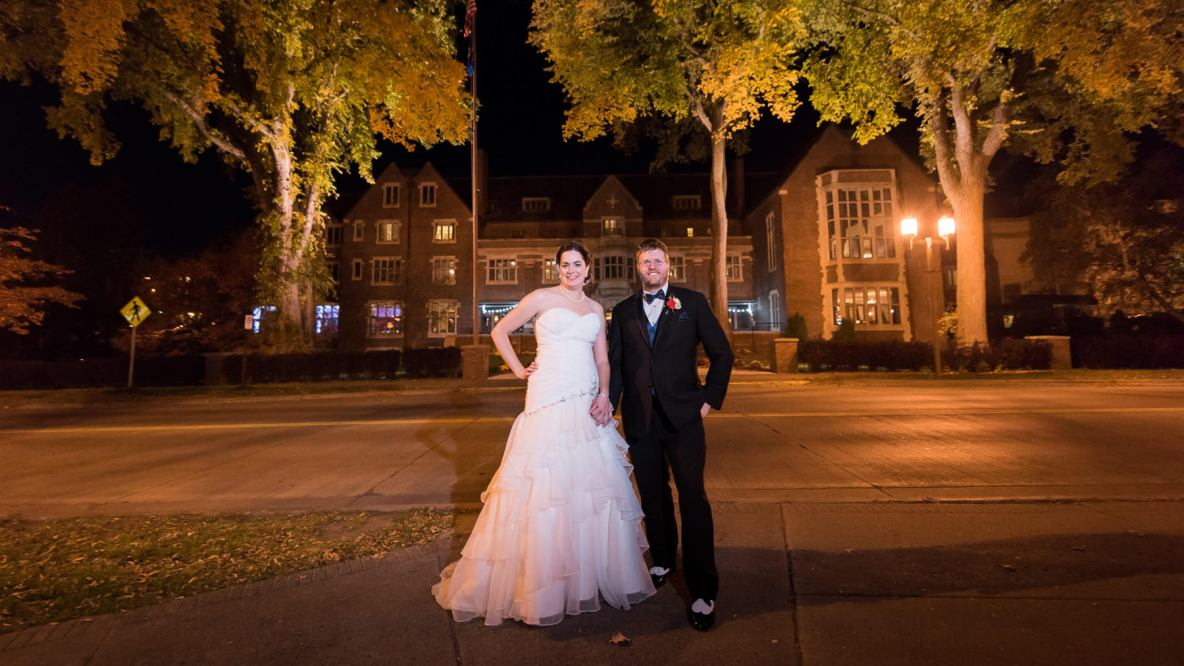 Bride and groom portrait outside on the street with large picturesque building in background.