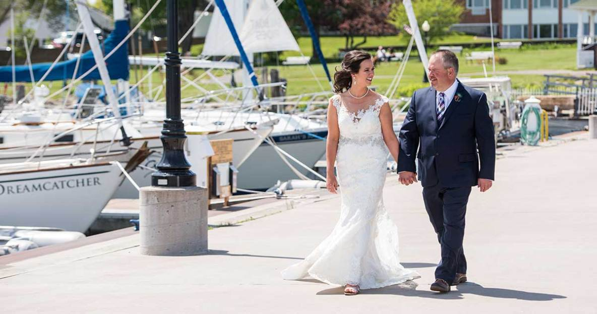 Bride and groom walking outside the marina in front of sailboats.