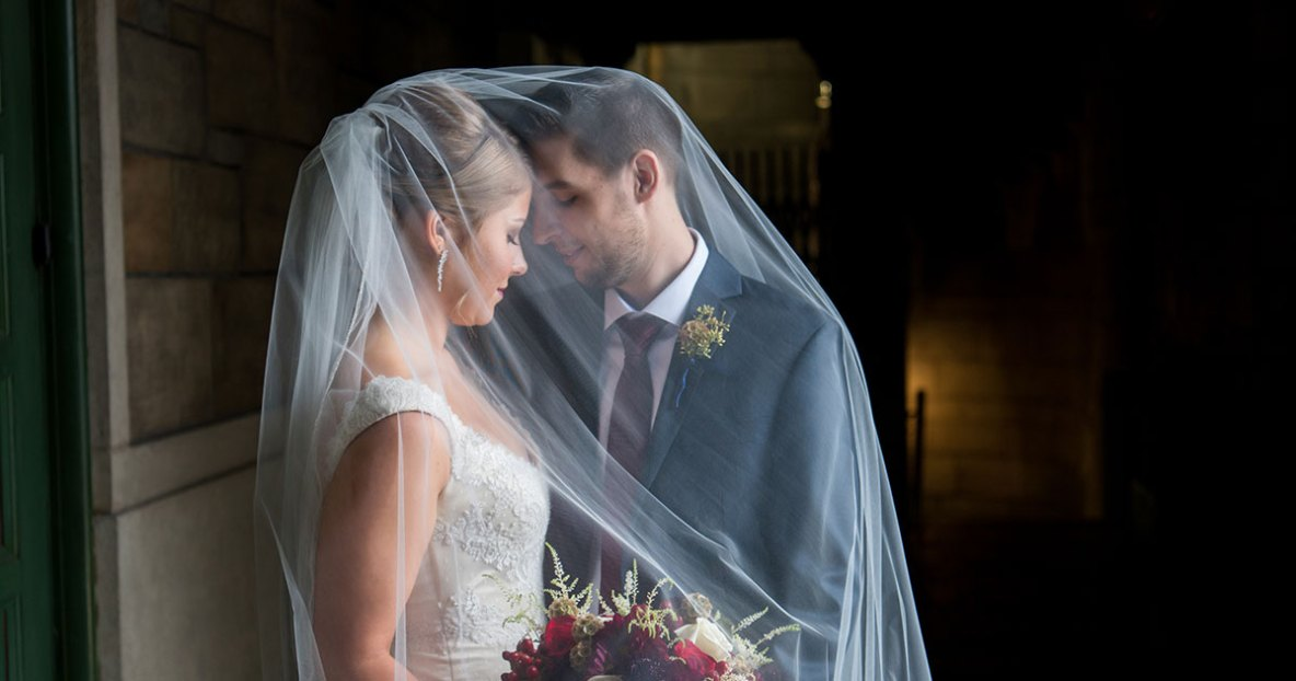 Bride and groom portrait indoors with veil covering faces.