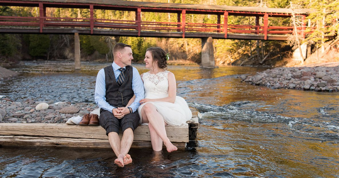 The bride and groom sitting in the Poplar River.