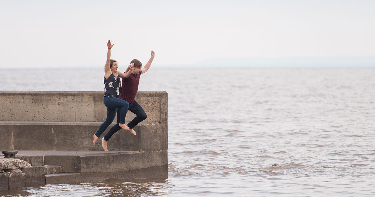 Photo of the engaged couple jumping into Lake Superior together.