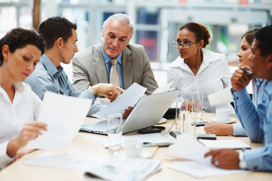 Business people discussing work on laptop at a meeting