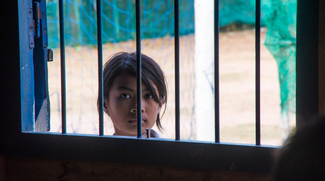 A female student looks in the window of the computer lab at CESHEO Svay Thom campus near Siem Reap, Cambodia