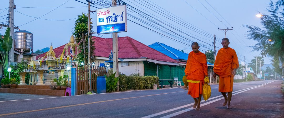 two monks walking down the road collecting alms in Sam Roi Yot, Thailand