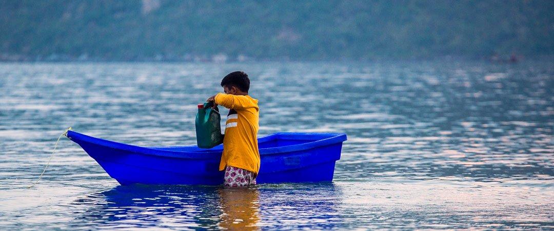 Man loading his rowboat Sam Roi Yot, Thailand