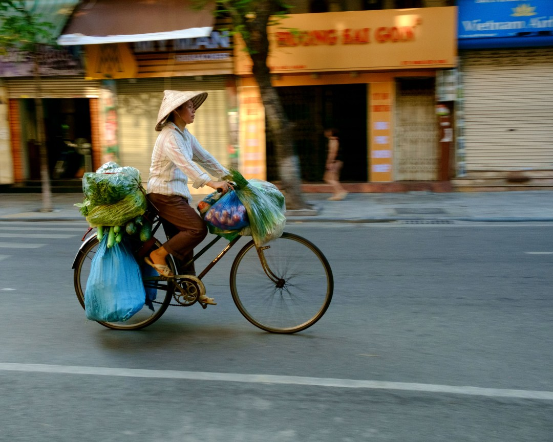 Photo of a woman carrying vegetables on a bicycle, Old French Quarter, Hanoi, Vietnam