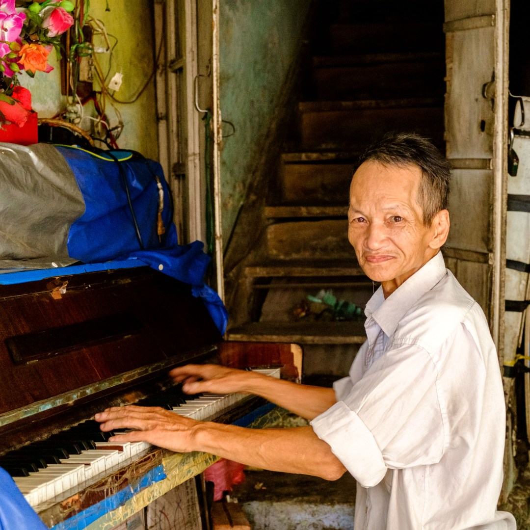 Photo of an old man playing a piano in his house, Old French Quarter, Hanoi, Vietnam