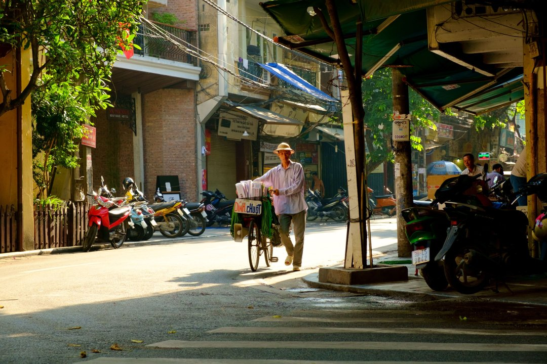 Man pushing his Bicycle down the street - Old French Quarter, Hanoi, Vietnam