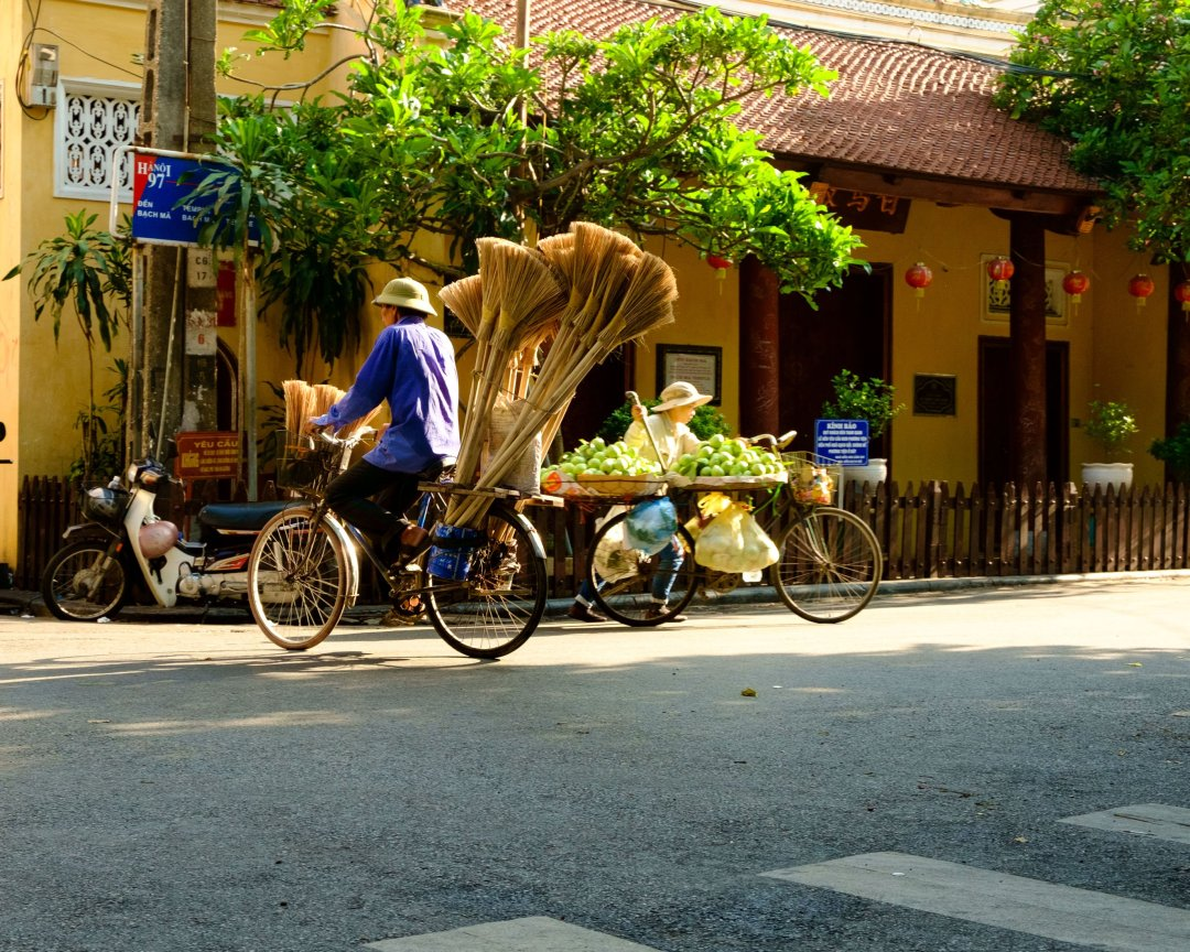 Man carrying brooms on his bicycle - Old French Quarter, Hanoi, Vietnam