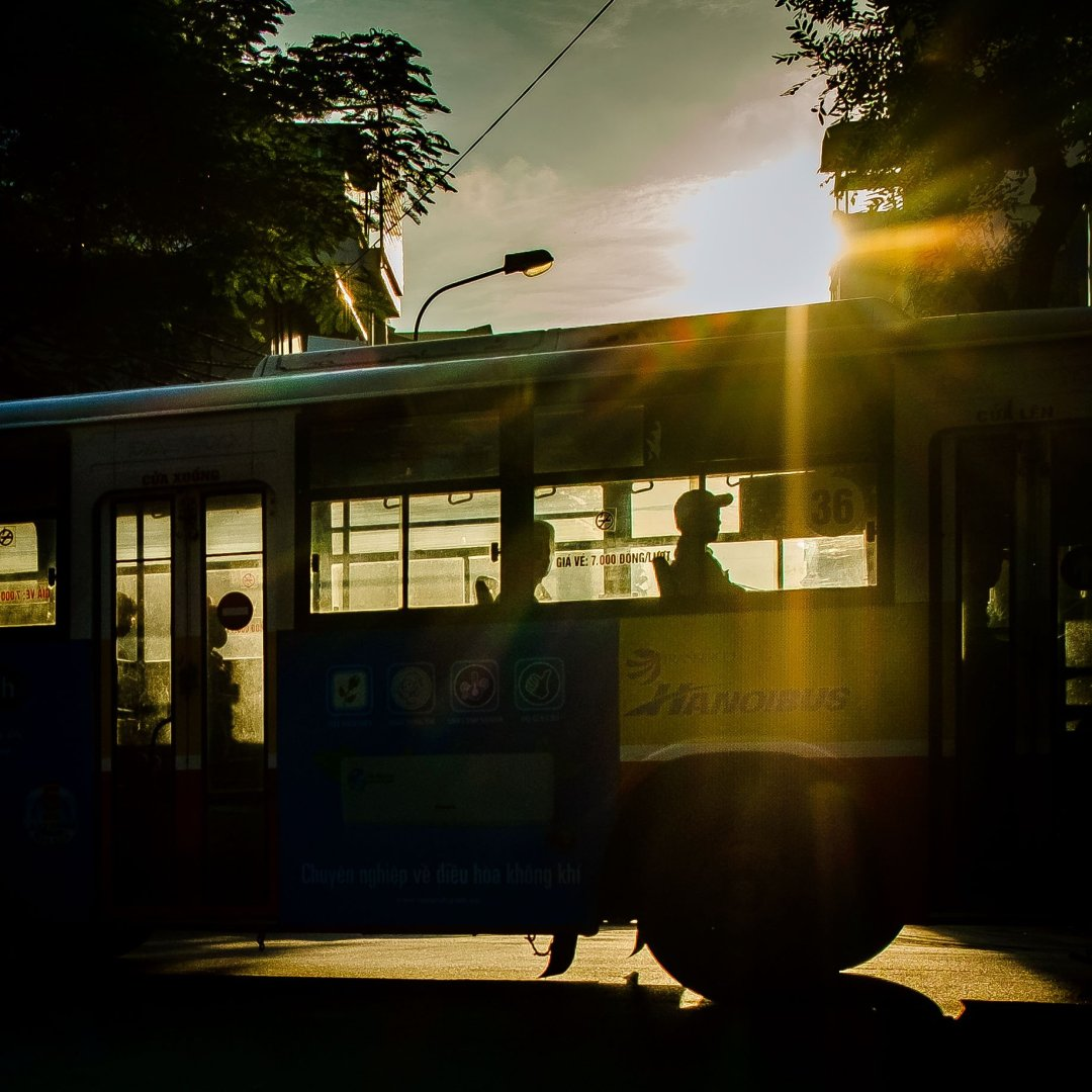 Photo of a bus and passengers silhouetted in an intersection, Old French Quarter, Hanoi, Vietnam