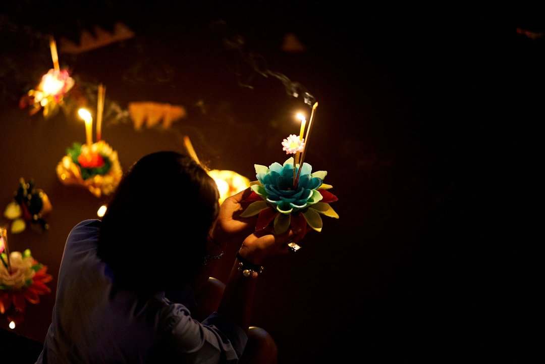Photo of a woman offering a prayer before launching her Krathong in Chiang Mai, Thailand during the Loi Krathong Festival on November 11, 2019 by Bryon Lippincott