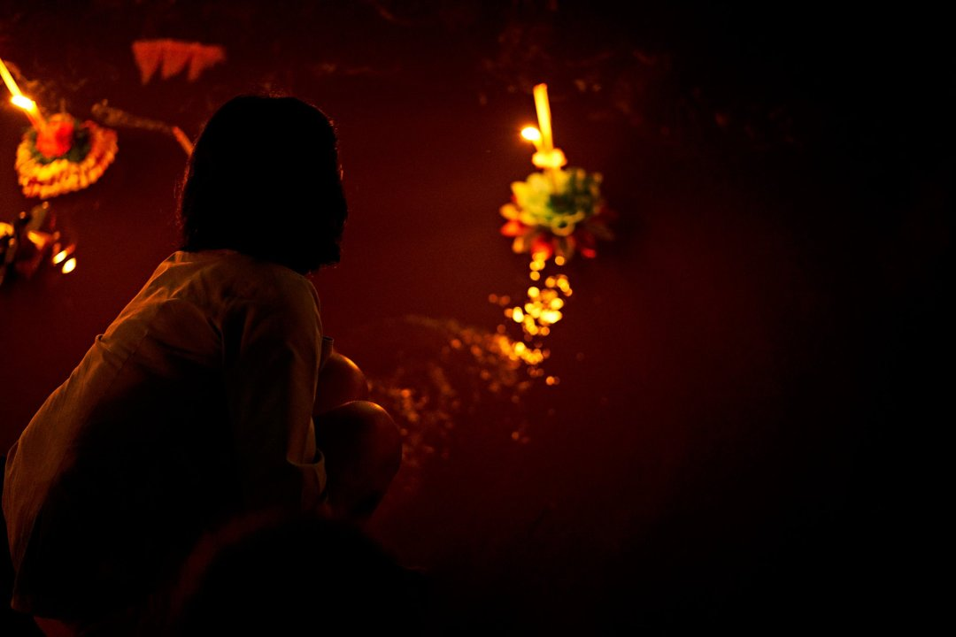 Photo of a woman splashing water with her hand to move her Krathong away from shore in Chiang Mai, Thailand during the Loi Krathong festival on November 11, 2019 by photographer Bryon Lippincott