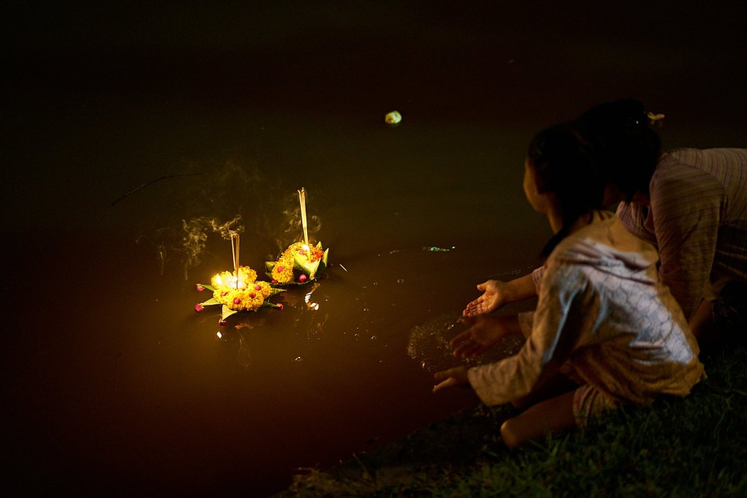 Photo of a mother and daughter launching a krathong made of banana leaves onto the moat in Chiang Mai, Thailand during the Loi Krathong Festival on November 11, 2019 by Bryon Lippincott