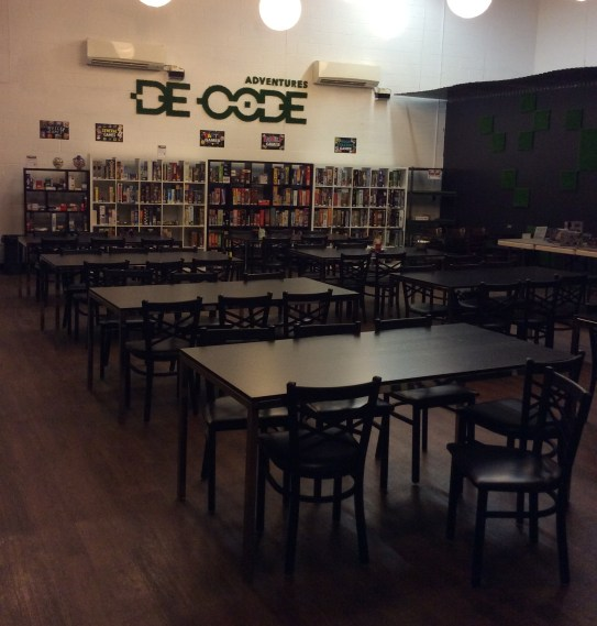 The tables and game shelf of De Code Adventures game room.