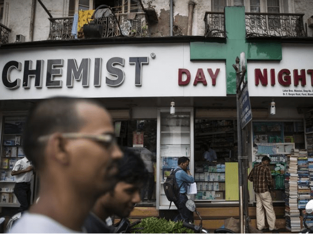 People walk past a chemist shop at a market in Mumbai