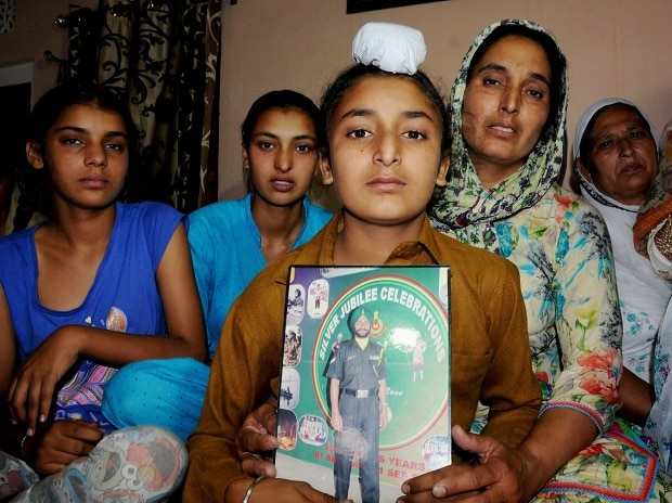 Wife Paramjit, son Sahildeep and daughters Khushdeep (L) and Simardeep of late Naib Subedar Paramjit Singh wait for arrival of his mortal remains at their village Vain Poin, Amritsar. He was killed by Pak Army and his body was mutilated. Photo: PTI