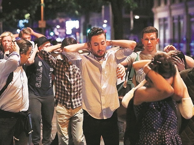 People leave the area with their hands up after the attack near London Bridge on Sunday. The attack started at 2158 local time (2058 GMT), according to authorities. Photo: reuters