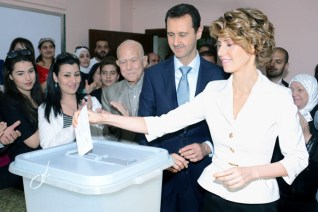 A handout picture released by the official Syrian Arab News Agency (SANA) shows Syrian President Bashar al-Assad (C) watching on as his wife Asma casts her vote at a polling station in Maliki, a residential area in the centre of the capital Damascus, in the country's presidential elections on June 3, 2014, which are expected to give Assad a sweeping win over two little-known challengers, state television reported. (AFP/SANA)