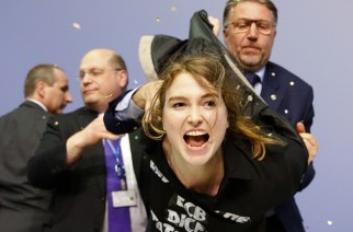 A protestor at an European Central Bank (ECB) press conference in April being apprehended after throwing confetti at ECB chief Mario Draghi