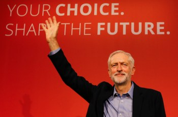 Jeremy Corbyn waves on stage after new is announced as the new leader of The Labour Party during the Labour Party Leadership Conference in London, Saturday, Sept. 12, 2015. Corbyn will now lead Britain's main opposition party. (AP Photo/Kirsty Wigglesworth)