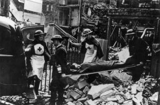 Second World War volunteers carry an injured person away from a bombed building