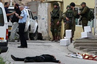 EDITORS NOTE: Graphic content / Israeli soldiers and police surround the body of one of two Palestinians who were killed after wounding an Israeli soldier in a knife attack before being shot dead by troops, an army spokeswoman said, at the entrance to the heavily guarded Jewish settler enclave of Tal Rumeda in the city centre of the West Bank town of Hebron on March 24, 2016. An Israeli soldier was detained after allegedly shooting a wounded Palestinian assailant in the head and killing him as he lay on the ground, the army said. In the video released by B'Tselem, an Israeli rights non-governmental organisation, the soldier appears to shoot the Palestinian again in the head without provocation as he lay wounded from a gun shot wound on the ground.    / AFP / HAZEM BADER        (Photo credit should read HAZEM BADER/AFP/Getty Images)