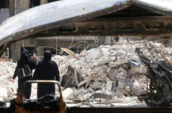 Women walk past damage near the Medecins Sans Frontieres (MSF)-backed al-Quds hospital after it was hit by airstrikes, in a rebel-held area of Syria's Aleppo, April 28, 2016.   Photo: Reuters