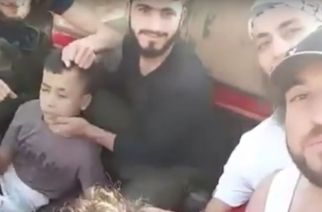 "U.S.-backed Syrian ""moderate"" rebels smile as they prepare to behead a 12-year-old boy (left), whose severed head is held aloft triumphantly in a later part of the video. [Screenshot from the YouTube video]"