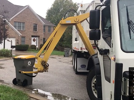 Sanitation worker uses a mechanical arm to empty a Bloomington solid waste cart. Screengrab from city of Bloomington video.