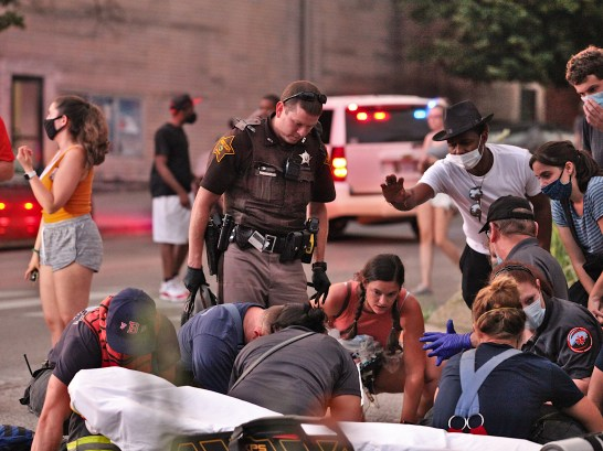 First responders attend to a woman lying in the crosswalk that connects the south and north sides of 6th Street just east of the courthouse square in downtown Bloomington.