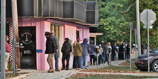 Looking north at the corner of 6th and Madison. Voters are standing in line to cast their ballots at Election Central a block north at 7th and Madison in Bloomington, Indiana on the first day of early voting, Oct. 6, 2020.