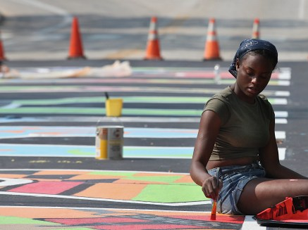 Siera Thompson helps paint the BLM mural on the IU campus street to be renamed Eagleson Avenue. (July 5, 2021)