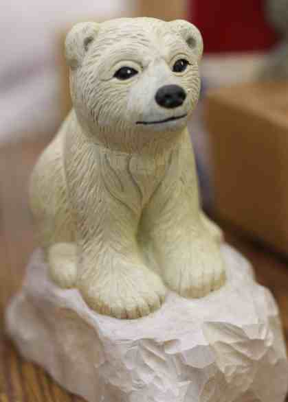 A carved wooden polar cub sits on an ice flow. Photo by Jess Gamari