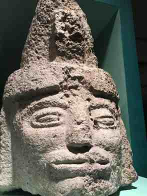 A limestone human figure wears a peaked headdress and sits on a central pillar, recalling the position it would have held on the wall of a Mayan temple 1,200 years ago. Photo by Kate Abbott