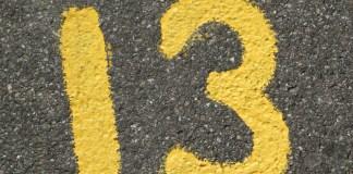 nummer dertien 13 in gele verf op asfalt