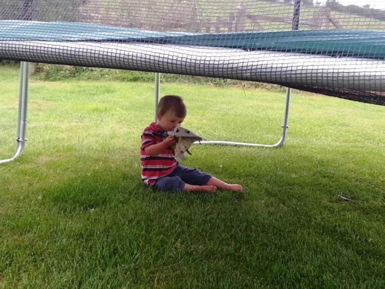 child under trampoline