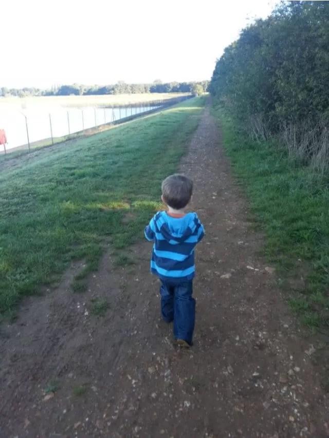 toddler in blue striped hoody walking alongside reservoir (1)
