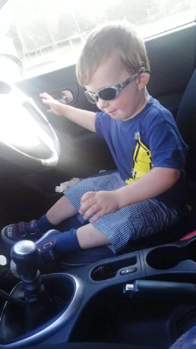 toddler in sunglasses in a car driving seat