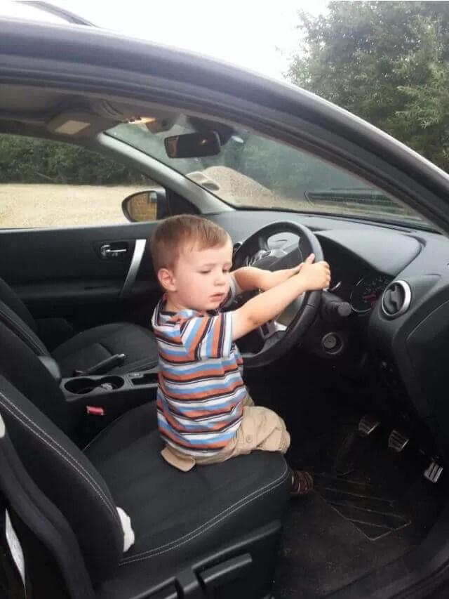 toddler pretending to drive car