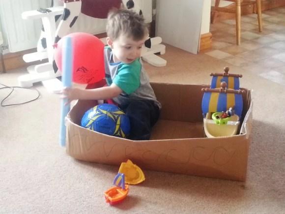 toddler in a cardboard box boat