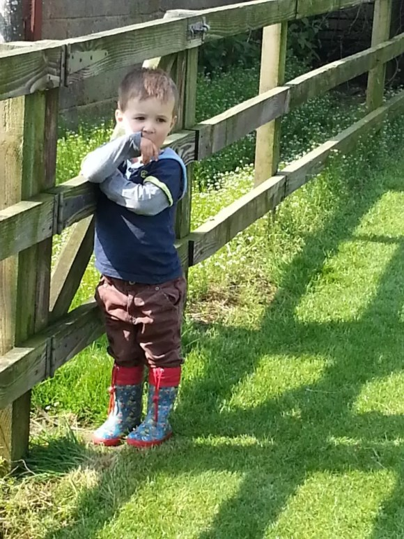 boy thinking by the gate