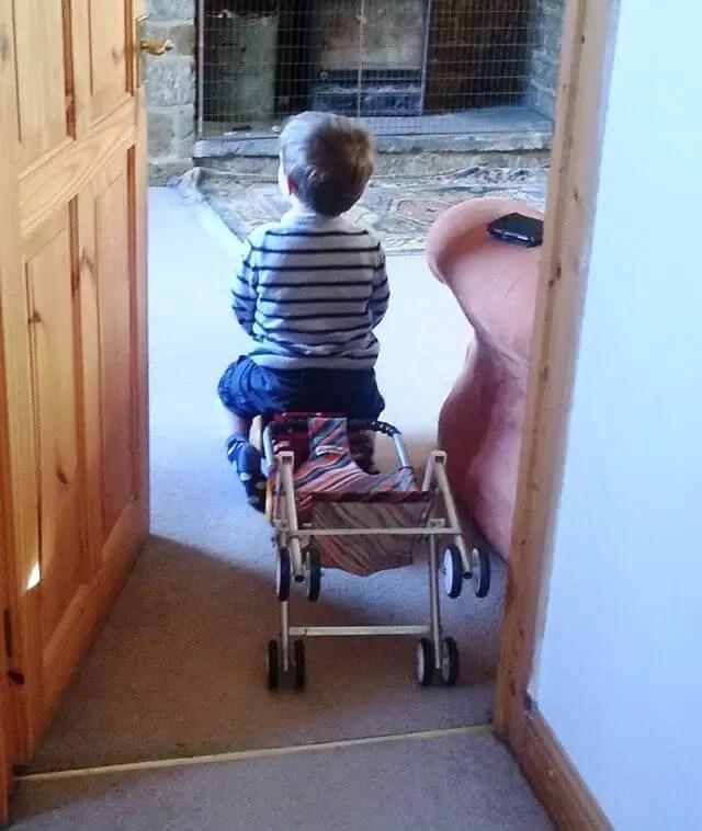 toddler sitting on toy pushchair