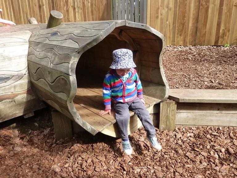 sitting inside the treetrunk playground equipment