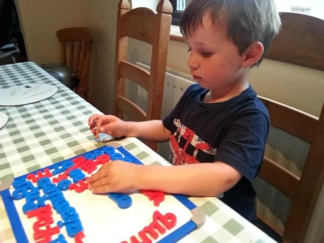 toddler playing with magnetic letters on white board