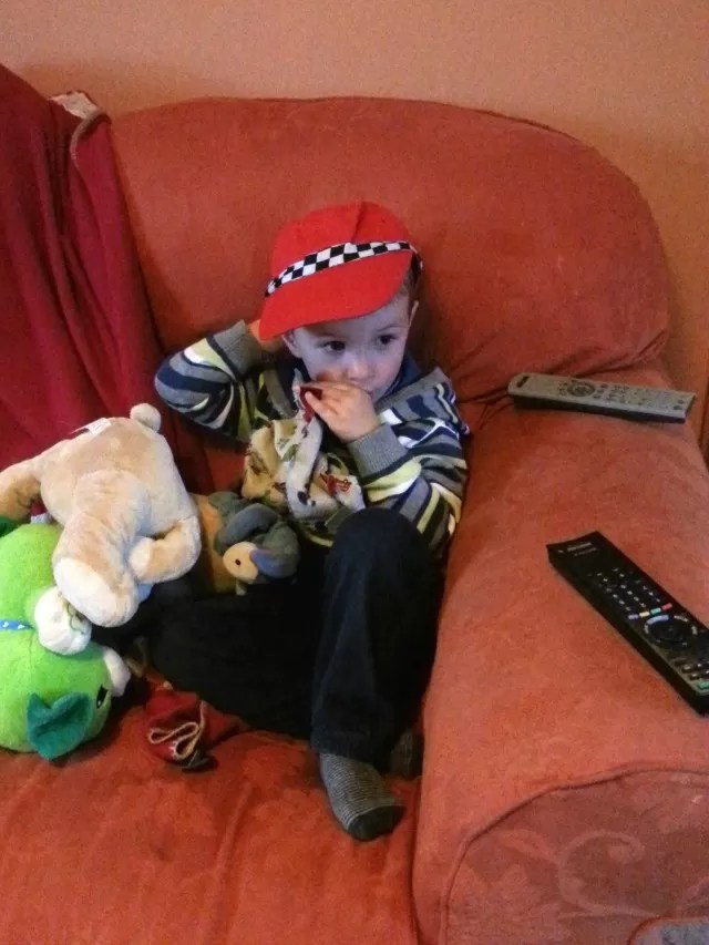 poorly boy resting with racing driver hat