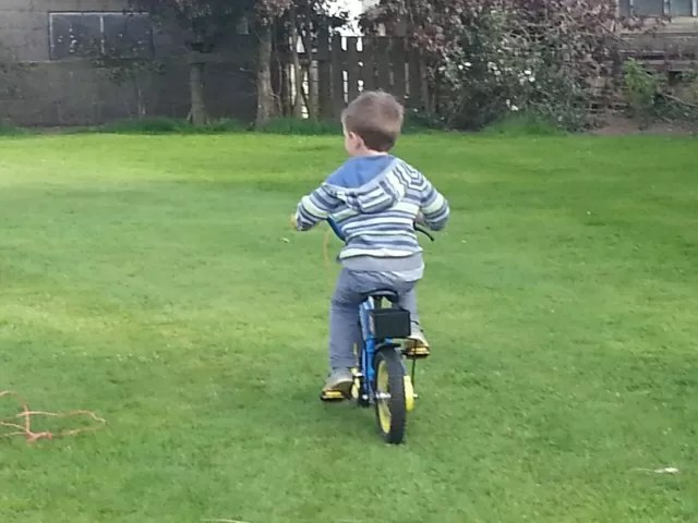 4 year old riding his bike round a lawn
